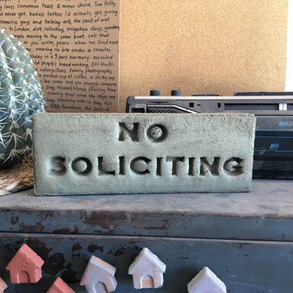 standard brick in green with the words no soliciting stamped into it