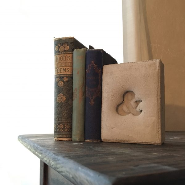 light grey concrete ampersand bookend holding up 3 antique books